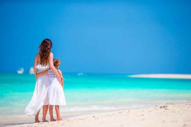 Mutter und tochter, die zeit am tropischen strand genießen