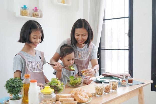 Mutter und tochter, die zu hause in der küche, glückliches familienasiatkonzept kocht