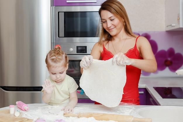 Mutter und tochter, die zu hause küche des teigs machen