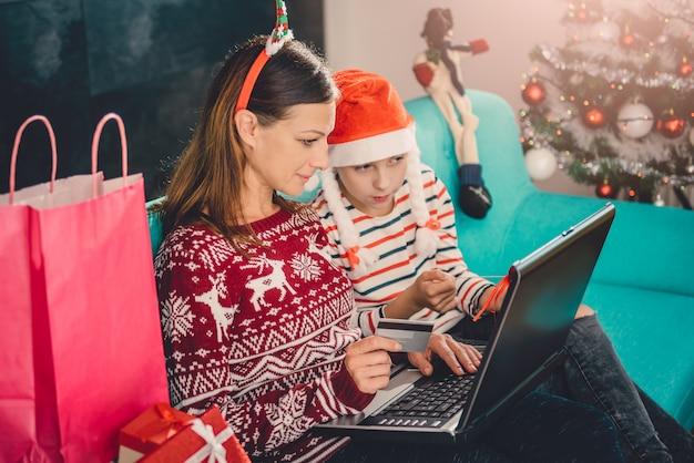 Mutter und tochter, die zu hause online während des weihnachten kaufen
