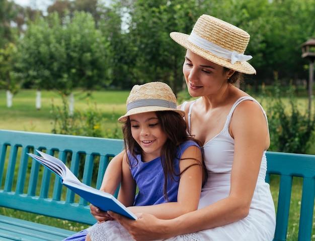Mutter und tochter, die zusammen auf bank lesen