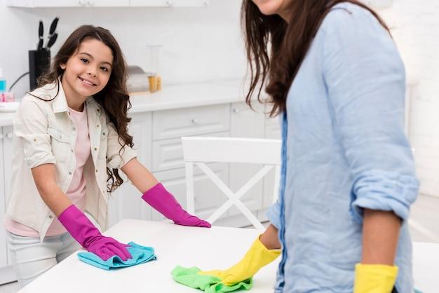 Mutter und tochter, die zusammen die küche säubern
