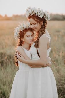 Mutter und tochter, die zusammen in den weißen kleidern mit borten und blumenkränzen in boho-art im sommer umarmen