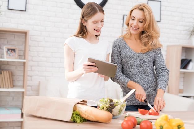 Mutter und tochter, die zusammen in der küche kochen.