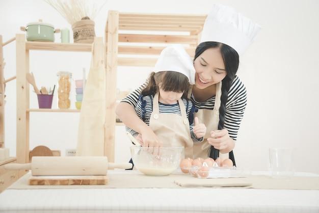 Mutter und tochter, die zusammen kochen, um einen kuchen im küchenraum zu machen.