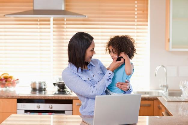 Mutter und tochter, die zusammen laptop und mobiltelefon in der küche verwenden