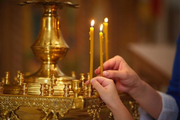 Mutter und tochter entzünden kerzen in der orthodoxen kirche, nahaufnahme von händen