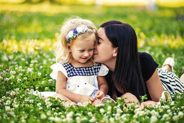 Mutter und tochter essen einen apfel in der natur. mutter und kind genießen den frühen frühling, essen apfel, glücklich.