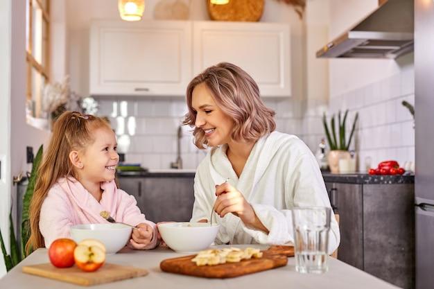 Mutter und tochter essen obst und brei. gesunde ernährung für kinder, morgenmahlzeit. kaukasische familie frühstückt in einer leichten modernen küche