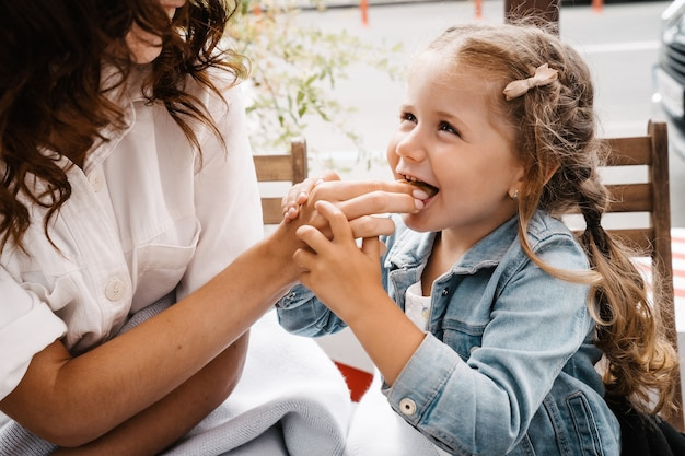 Mutter und tochter essen pommes in einem straßencafé