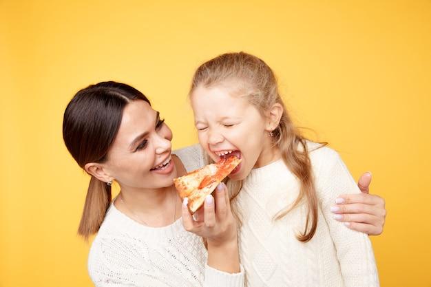 Mutter und tochter essen zusammen pizza