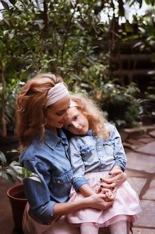 Mutter und tochter. familiärer blick. frau umarmt und küsst ihre tochter