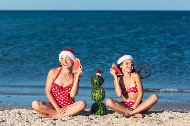 Mutter und tochter feiern sommerweihnachten am strand und essen wassermelone. sommerschneemann aus wassermelonen.