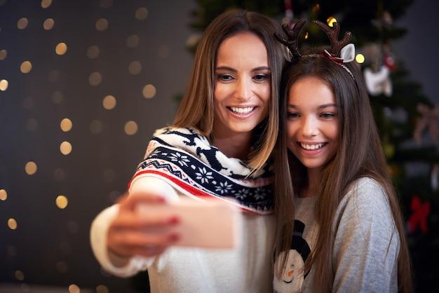 Mutter und tochter feiern weihnachten zu hause und machen selfie