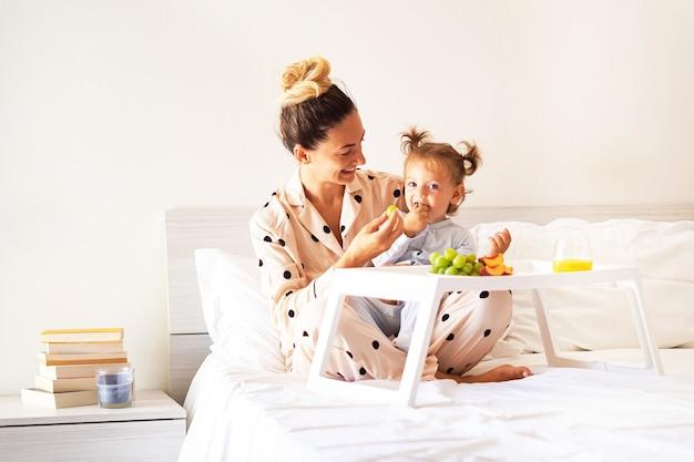 Mutter und tochter frühstücken im bett mit früchten im schlafanzug