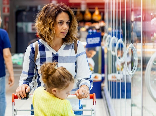 Mutter und tochter für lebensmittel im supermarkt einkaufen