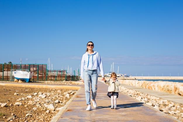 Mutter und tochter gehen am strand spazieren