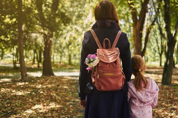 Mutter und tochter gehen an einem herbsttag im wald spazieren. sie gehen auf einem weg und tragen rucksäcke.