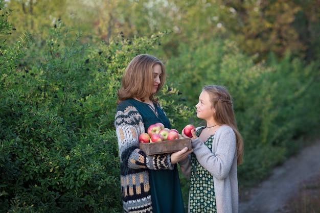 Mutter und tochter gehen auf äpfeln spazieren