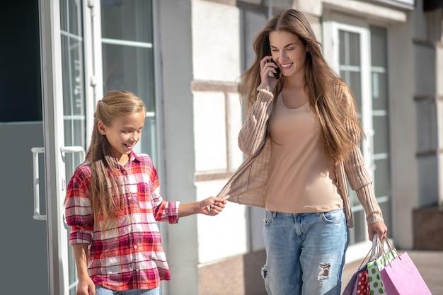 Mutter und tochter gehen mit einkaufstüten die straße entlang