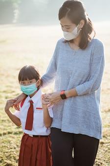 Mutter und tochter gehen zusammen und tragen gesichtsmaske