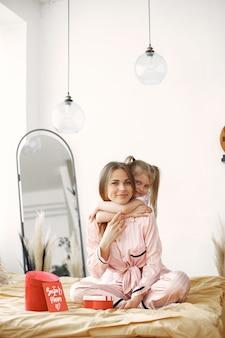 Mutter und tochter genießen auf dem bett. halten rote geschenkbox. muttertag.