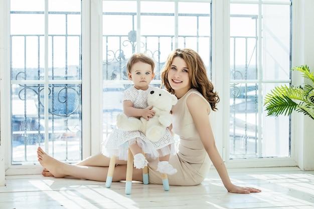 Mutter und tochter glücklich und schönes zuhause zusammen spielen auf dem boden auf fensterhintergrund