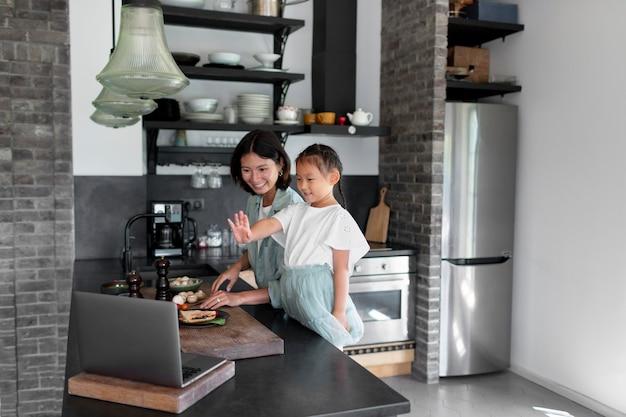 Mutter und tochter haben einen videoanruf aus ihrer küche
