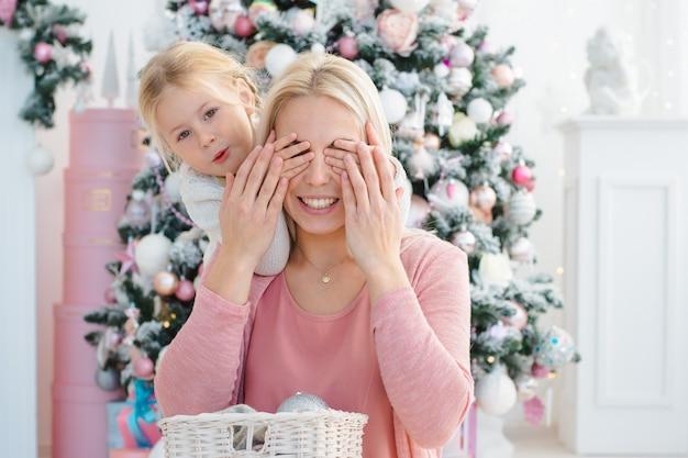 Mutter und tochter haben spaß am weihnachtsbaum, der sich für den feiertag vorbereitet