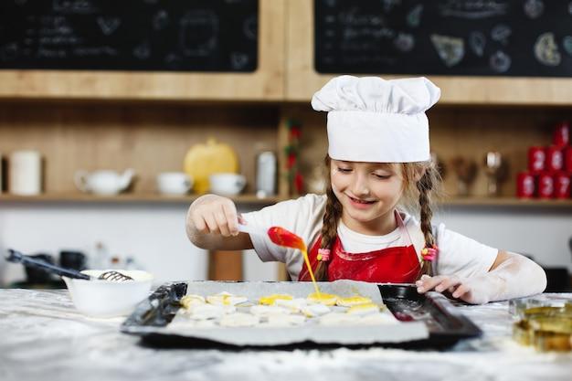 Mutter und tochter haben spaß am zubereiten von keksen mit milch an einem esstisch in der gemütlichen küche
