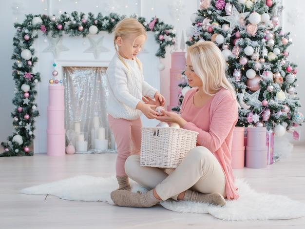 Mutter und tochter haben spaß auf dem hintergrund des weihnachtsbaums, der für den feiertag sich vorbereitet