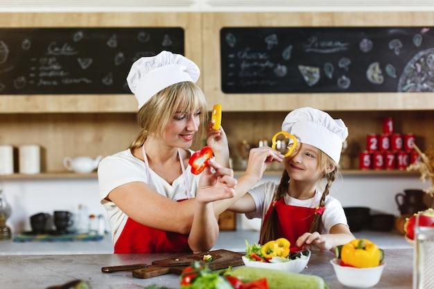 Mutter und tochter haben spaß in der küche und kochen verschiedenes gemüse für ein abendessen