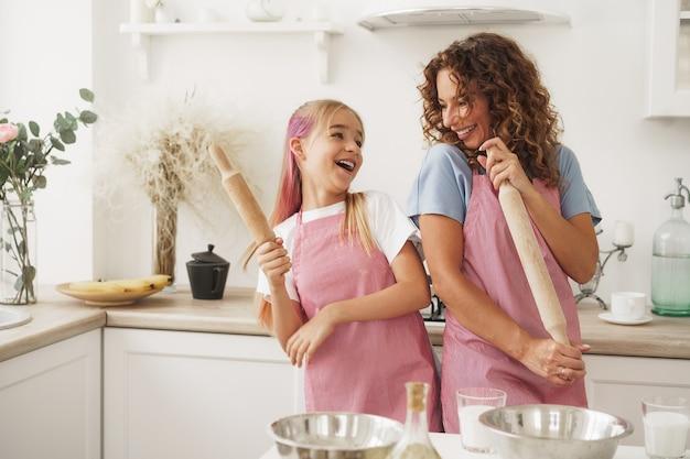 Mutter und tochter haben spaß mit nudelholz in der küche beim kochen