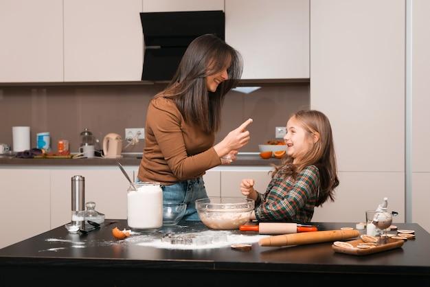 Mutter und tochter haben spaß zusammen in der küche, während sie einige süßigkeiten vorbereiten