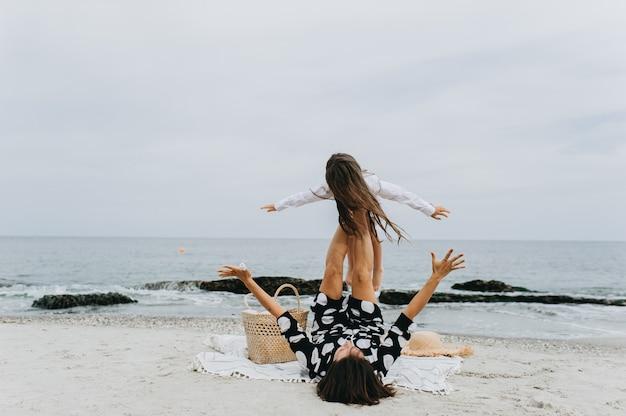 Mutter und tochter händchen haltend und zu fuß am strand.