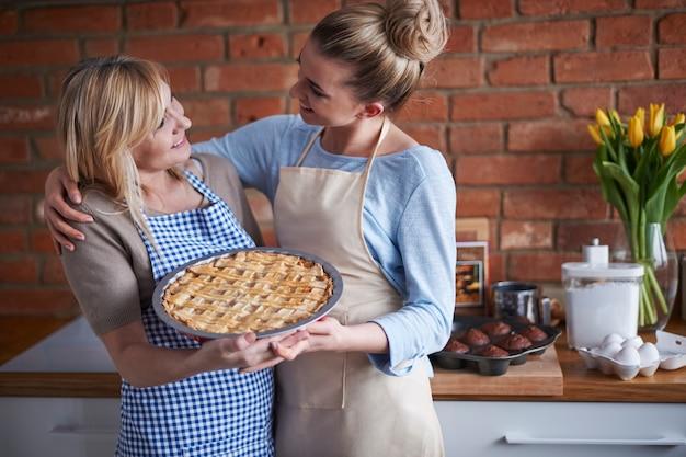 Mutter und tochter halten einen kuchen
