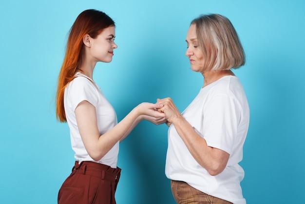 Mutter und tochter halten händchen in weißen t-shirts familie zusammen