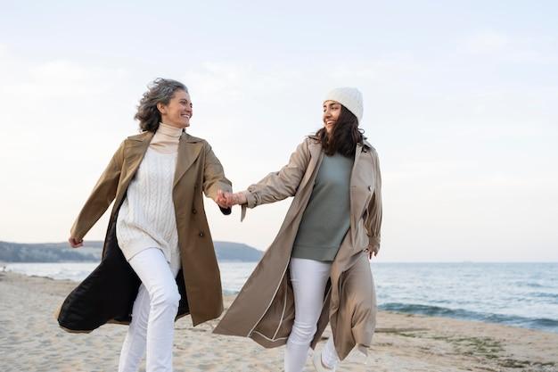 Mutter und tochter halten händchen, während sie zusammen am strand sind