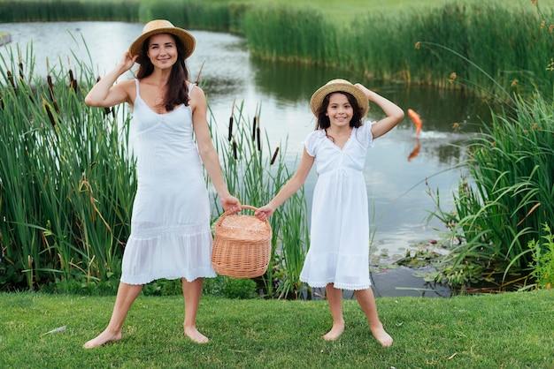Mutter und tochter halten picknickkorb am see