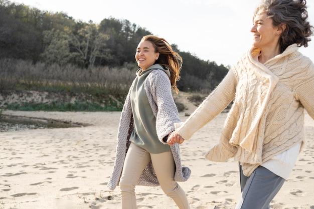 Mutter und tochter halten sich am strand an den händen