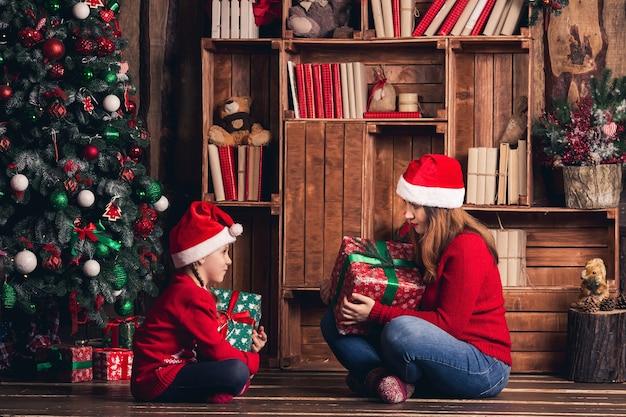 Mutter und tochter halten weihnachtsgeschenke