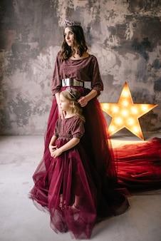 Mutter und tochter im bild der königin und prinzessin kleiden sich in den farben von marsala mit einer langen schleppe auf dem dachboden