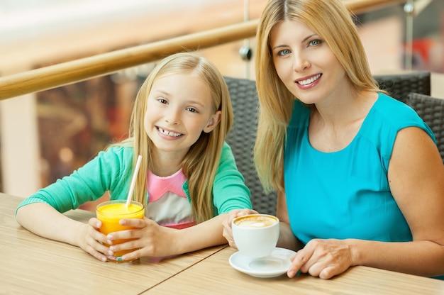 Mutter und tochter im café. fröhliche mutter und tochter, die sich zusammen im café entspannen?