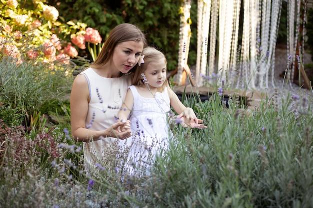 Mutter und tochter im lavendel umarmen sich und haben spaß im freien in der natur
