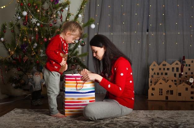 Mutter und tochter im roten pullover für weihnachten am weihnachtsbaum.