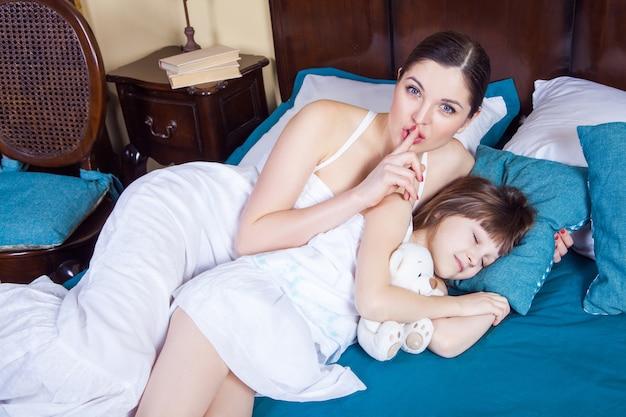 Mutter und tochter im schlafzimmer. mutter zeigt hash-zeichen an der kamera, tochter schloss die augen und schläft. studioaufnahme