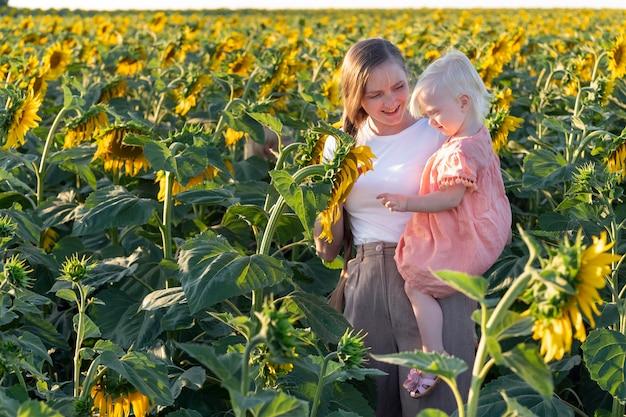 Mutter und tochter im sonnenblumenfeld. porträt von mutter und kind über die natur. zärtlichkeit und sorgfalt.