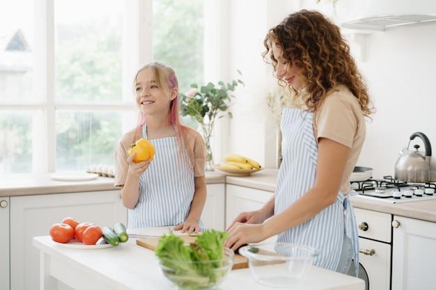 Mutter und tochter im teenageralter, die gemüsesalat in der küche zubereiten
