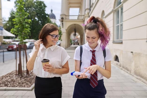 Mutter und tochter im teenageralter gehen zusammen auf der stadtstraße. sprechende mutter und studentin, eltern und kind diskutieren über schule, studium