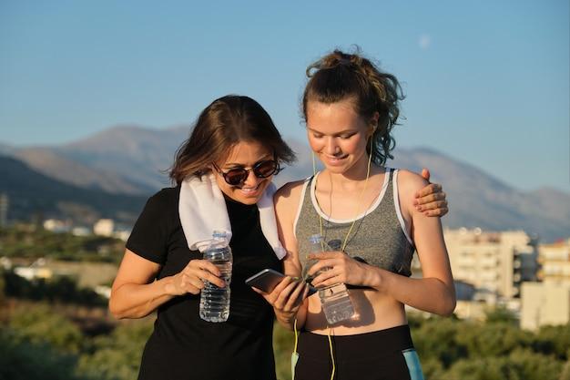 Mutter und tochter im teenageralter trinken wasser an heißen sommertagen nach dem training und joggen im freien in den bergen